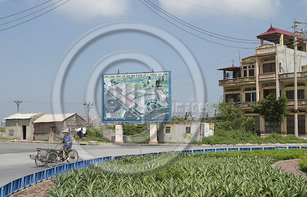 Bac Ninh-Vietnam-Viet Nam - 27 July 2005---Big poster site / board to illustrate the development of a new residential area, at a roundabout with a cyclist at the outskirts of Bac Ninh; project area of 'Wastewater Management in Provincial Urban Centers' - Technical Assistance on behalf of GTZ by GFA Management  & Associates---infrastructure, housing, traffic---Photo: Horst Wagner/eup-images