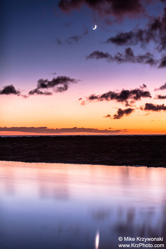 Colorful sunset w/ reflection on tide pool at the beach, North Shore, Oahu, Hawaii