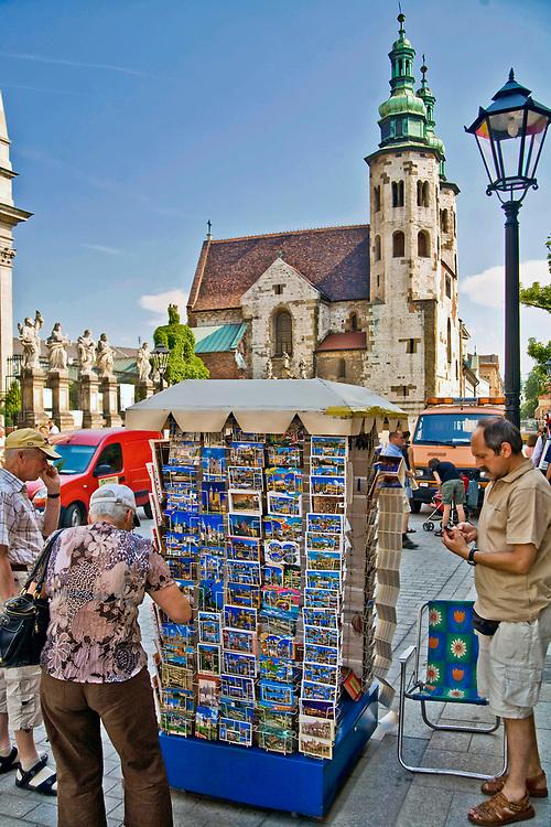 Sprzedawca pamiątkowych pocztówek z Krakowa, w głębi kościół św. Andrzej, ulica Grodzka w Krakowie