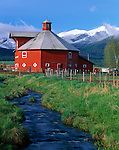 Wallowa County, OR<br /> A red octagonal barn in the Wallowa Valley (built in 1906) with the Wallowa Mountain in the distance.