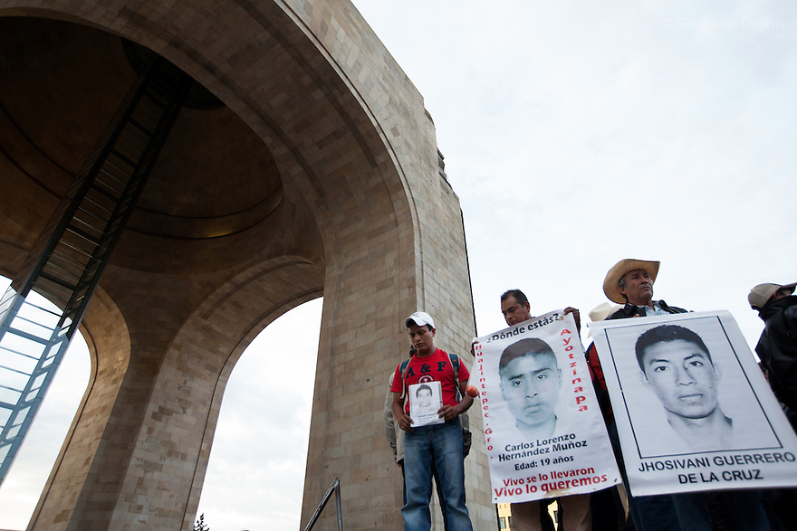 Parents and relatives of the missing students from Ayotzinapa's teacher training college, stood on a platform in front of the The Monument to the Revolution holding images of the missing students during a march to mark the three months since the disappearance of 43 Ayotzinapa's teaching college students in Mexico City on December 26, 2014. The 43 students went missing on Sept. 26 after confrontations in which police gunfire killed six people and wounded at least 25 in Iguala, in Guerrero state. Alexander Mora Venancio, one of the 43 missing students of Ayotzinapa, has been identified and confirmed dead by authorities.  Many are demanding justice and that the search for the 42 missing students continue until there is concrete evidence to the contrary. Mexico – officially - lists more than 20 thousand people as having gone missing since the start of the country's drug war in 2006, and the search for the missing students has turned up other, unrelated mass graves. (Photo by Benedicte Desrus)