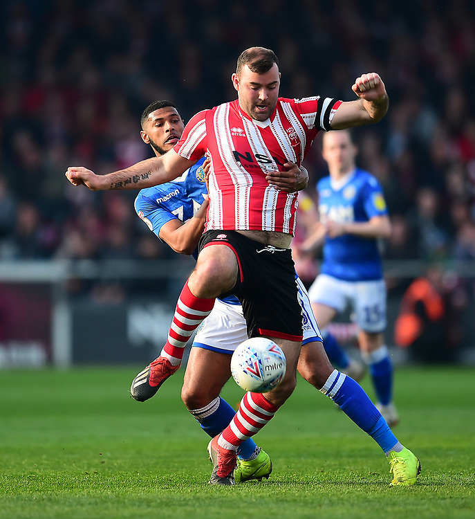 Lincoln City's Matt Rhead battles with  Macclesfield Town's Zak Jules<br /> <br /> Photographer Andrew Vaughan/CameraSport<br /> <br /> The EFL Sky Bet League Two - Lincoln City v Macclesfield Town - Saturday 30th March 2019 - Sincil Bank - Lincoln<br /> <br /> World Copyright © 2019 CameraSport. All rights reserved. 43 Linden Ave. Countesthorpe. Leicester. England. LE8 5PG - Tel: +44 (0) 116 277 4147 - admin@camerasport.com - www.camerasport.com