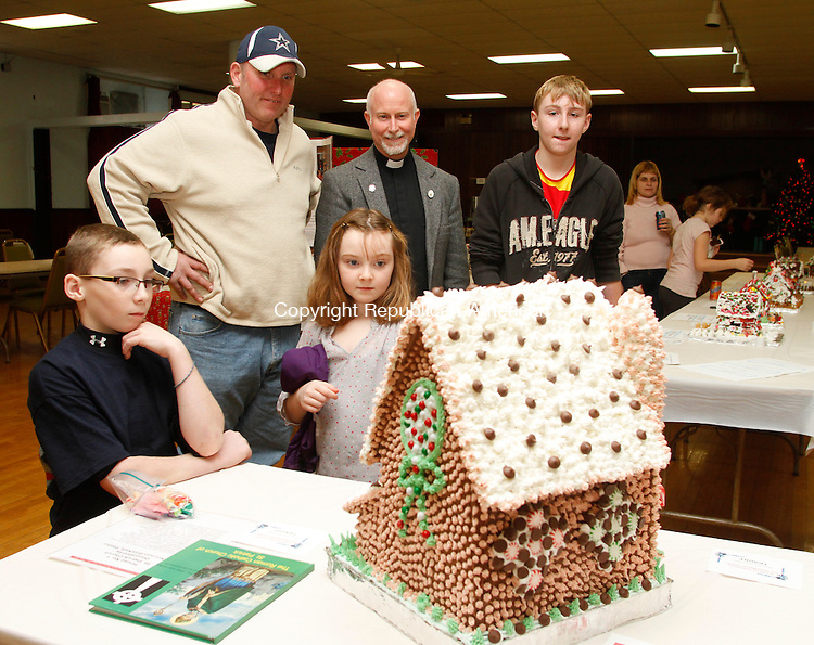 WATERBURY CT.- 07 DECEMBER 2013 - 120713JW03 - After decorating their own house, Frank Bethin of Thomaston, with his children Ryan Bethin, Haley Bethin and Ian Bethin look at a gingerbread house of St. Patrick's Church with St. Patrick's Church pastor Rev. Norman Brockett during the Gingerbread Wonderland Tour Saturday afternoon at the church.<br /> Jonathan Wilcox Republican-American