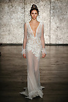 Model walks runway in a v front & back crochet lace long sleeve sheath, from Inbal Dror Fall 2018 bridal collection on October 5, 2017; during New York Bridal Fashion Week.