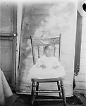 BABY ON A CHAIR. This portrait of a baby catches the hem of a woman's dress at the left edge of the frame, hinting that this youngster was not accustomed to sitting up, especially in a grown-up's chair.<br /> <br /> Photographs taken on black and white glass negatives by African American photographer(s) John Johnson and Earl McWilliams from 1910 to 1925 in Lincoln, Nebraska. Douglas Keister has 280 5x7 glass negatives taken by these photographers. Larger scans available on request.