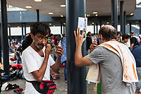 Two men shaving at the Budapest Railway station. Thousands of migrants have been camped out at the station waiting for trains to Germany.