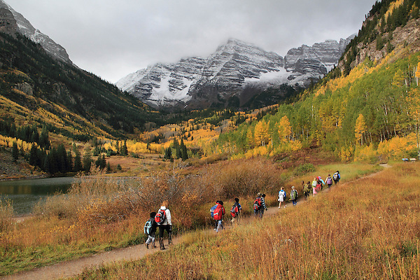 Group of Caucasian students and teacher hiking along Maroon Lake, with South and North Maroon Peaks behind, near Aspen, Colorado, USA