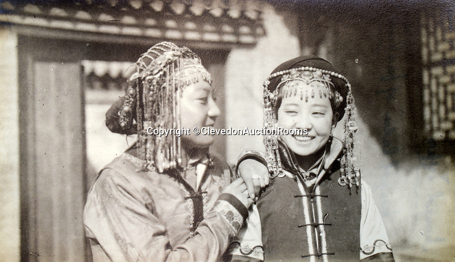 BNPS.co.uk (01202 558833)<br /> Pic: ClevedonAuctionRooms/BNPS<br /> <br /> Mongolian women in traditional dress.<br /> <br /> Rev Francis John Griffith travelled as a Missionary aroud Outer Mongolia in the 1920's.<br /> <br /> A fascinating collection of early 20th century photos of Mongolia and China which were taken by a British vicar doing missionary work have been unearthed after 97 years.<br /> <br /> Through his famine relief work Reverend Francis John Griffith was able to get a remarkable insight into the lives of the native population and their nomadic existence.<br /> <br /> His encounters were captured using a handheld camera that he carried with him at all times.<br /> <br /> In one image a family goes about its business outside the hut that is their home, while another image is of a man riding a camel which was the typical method of transport.<br /> <br /> Revd Griffith was able to get native elders to sit for him in portraits and there are intimate snaps of women and children wearing elaborate native headdresses.<br /> <br /> As well as the people, Revd Griffith took an interest in the surroundings and photographed temples and prominent buildings in addition to the vast, desert landscape.