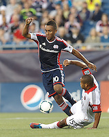 D.C. United defender Ethan White (15) slide tackle on New England Revolution midfielder Juan Agudelo (10). In a Major League Soccer (MLS) match, the New England Revolution (blue) tied D.C. United (white), 0-0, at Gillette Stadium on June 8, 2013.