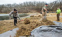Jesus Sandoval (from left), 11, rakes up grass Wednesday, March 18, 2020, while doing landscaping work with Derrick Madison and father Alfredo Sandoval at Lake Atalanta Park in Rogers. Check out nwaonline.com/200319Daily/ for today's photo gallery.<br /> (NWA Democrat-Gazette/Ben Goff)