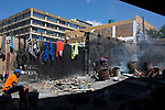 MABONENG, SOUTH AFRICA - MARCH 21: Homeless people cook food under a bridge in Maboneng district on March 21, 2016 in downtown Johannesburg, South Africa.  A former derelict industrial area, and a no-go area after dark, it is now a vibrant area with artists, businesses, galleries and tourists. A racially mixed cultural hub with markets on the weekend. Maboneng is the idea of young entrepreneur Jonathan Liebmann, and he owns and controls most of the buildings in the area. (Photo by Per-Anders Pettersson/Getty Images)