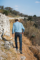 Archeologist Aurelio Lopez walks along a retaining wall in Sector A, part of the Plaza #1. Archeological site Tepeticpac, Tlaxcala, Mexico