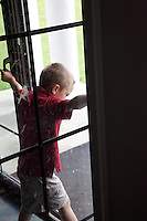 Polish boy age 6 having a thoughtful moment looking out glass door. Zawady Central Poland