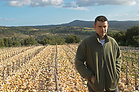 Frédéric Pourtalié Domaine de Montcalmes in Puechabon in vineyard of Dom Saint Sylvestre. Terrasses de Larzac. Languedoc. Young Mourvedre grape vine variety. Terroir soil. Owner winemaker. France. Europe. Vineyard. Soil with stones rocks. Galets.