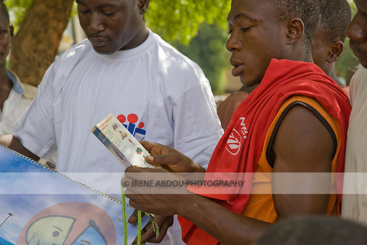An HIV/AIDS prevention volunteer (left) talks to men in Yankaba market in Kano, Nigeria, about how partner reduction reduces chances of HIV/AIDS transmission.  He uses a pictoral flipchart designed for low-literacy audiences by the Society for Family Health (SFH), Nigeria's largest indigenous non-profit and affiliate of the international social marketing organization, Population Services International (PSI).
