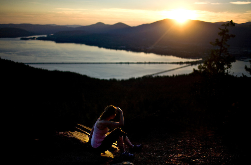 A woman hiker sits atop the Gold Hill in Trail overlooking Lake Pend Oreille and Sandpoint in the Idaho Panhandle.