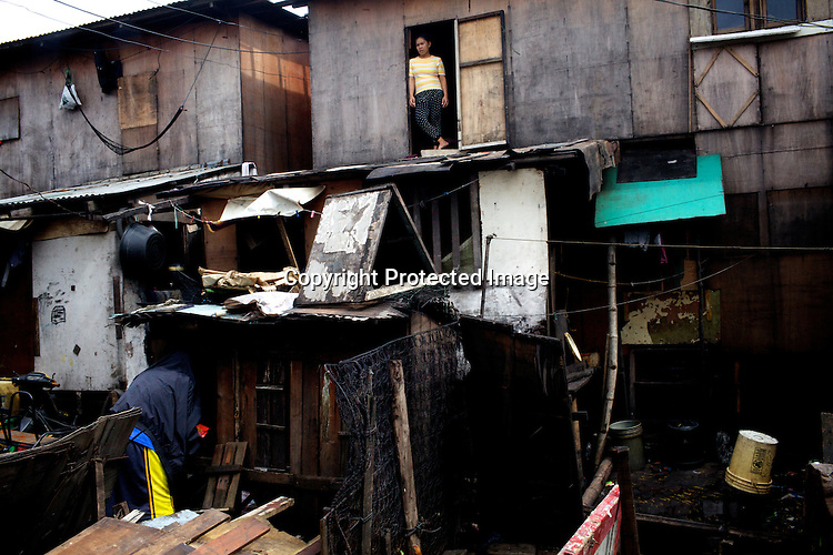 A woman stands outside to speak to her husband standing in the slums of Smokey Mountain-II in Manila in Philippines. Photo: Sanjit Das