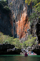Tourists canoeing by the limestone cliffs in the national marine park of Phang Nga Bay, Thailand