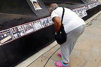 A woman takes a look of photographs as relatives of missing people and others affected by the Colombian conflict stand near photographs commemorating the International Day of the people disappeared on August 30, 2016. in Medellin, Colombia. Photo by VIEWpress