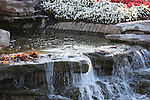 A manmade rock ledge waterfall with red fall leaves that have accumulated in the stream