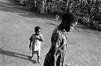 Youth in the bush. Children are susceptible to many health concerns in Uganda, especially in rural environments. Medical resources to treat complex disease like HIV/AIDS and malaria or even simple concerns like parasites or the flu in rural areas are almost non-existent.  Village Nasamuri. Kamuli District, Uganda, Africa. June 2004 © Stephen Blake Farrington