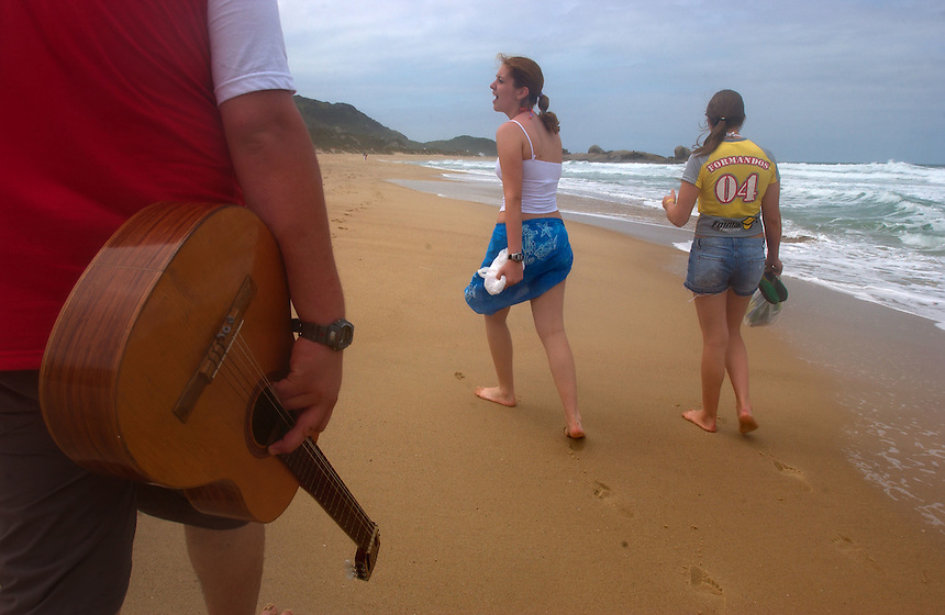Guitar-toting Brazilian youths stroll Praia Mole, or Soft Beach, on Santa Catarina Island in southern Brazil. The island has long been a destination for beach-loving Brazilians. (Kevin Moloney for the New York Times)