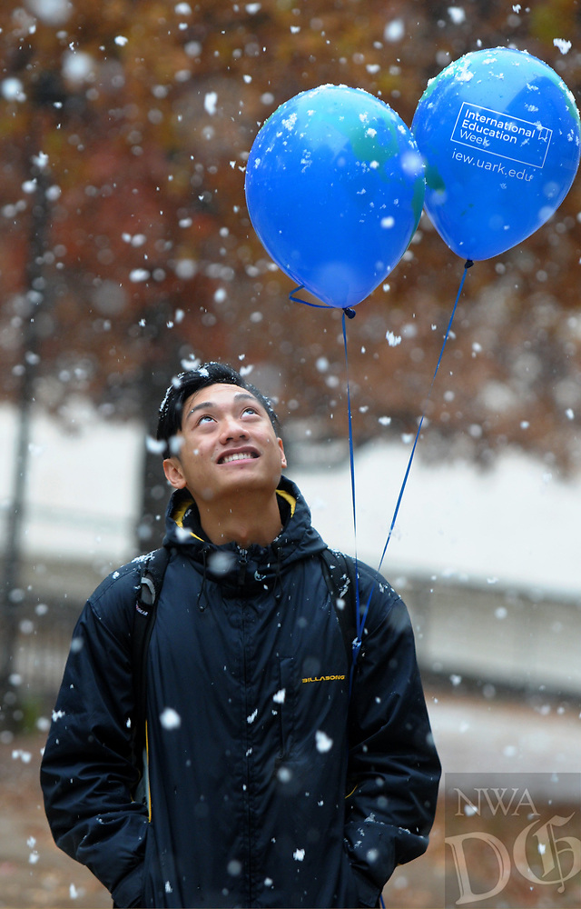 NWA Democrat-Gazette/DAVID GOTTSCHALK Vince Sayarath, a senior at the University of Arkansas, looks up at the snowflakes Monday, November 12, 2018, as he walks across campus in Fayetteville. Portions of Northwest Arkansas received a mix of rain, snow and sleet during the day.