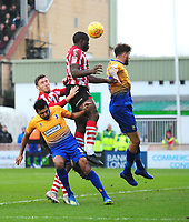 Lincoln City's John Akinde gets above Mansfield Town's Malvind Benning, left and Ryan Sweeney<br /> <br /> Photographer Andrew Vaughan/CameraSport<br /> <br /> The EFL Sky Bet League Two - Lincoln City v Mansfield Town - Saturday 24th November 2018 - Sincil Bank - Lincoln<br /> <br /> World Copyright &copy; 2018 CameraSport. All rights reserved. 43 Linden Ave. Countesthorpe. Leicester. England. LE8 5PG - Tel: +44 (0) 116 277 4147 - admin@camerasport.com - www.camerasport.com