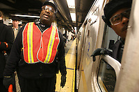 "NYC transit worker Kenneth Hoyt does 'platform control' during rush hour on the uptown Lexington Ave. line at the Grand Central subway station on the same day that the contract between the Transit Worker's Union (TWU) and the NYC Metropolitan Transportation Authority (MTA) expired on Friday, December 16, 2005.  The TWU's leadership has decided to continue with contract negotiations for at least another four days before declaring a strike, and Hoyt, a subway conductor who has been with the MTA for 36 years, said he hopes the union doesn't ""give in."""