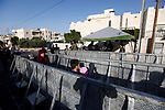 Palestinians make their way through an Israeli checkpoint along Israel's controversial separation barrier to attend the last Friday prayer of the holy fasting month of Ramadan in Jerusalem's Al-Aqsa mosque, in Bethlehem in the occupied West Bank, on June 8, 2018. Ramadan is sacred to Muslims because it is during that month that tradition says the Koran was revealed to the Prophet Mohammed. The fast is one of the five main religious obligations under Islam. Muslims around the world will mark the month, during which believers abstain from eating, drinking, smoking and having sex from dawn until sunset. Photo by Wisam Hashlamoun