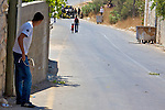 A Palestinian youth waits for a Palestinian man with a young girl to move out of the line of fire before continuing to hurl stones at Israeli soldiers during protests against the expansion of the nearby Jewish settlement of Halamish, in the West Bank village of Nabi Saleh near Ramallah on 02/07/2010.