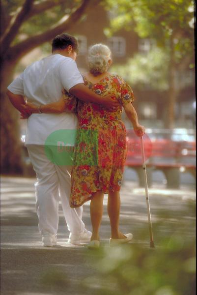 nurse helping elder patient walk outdoors