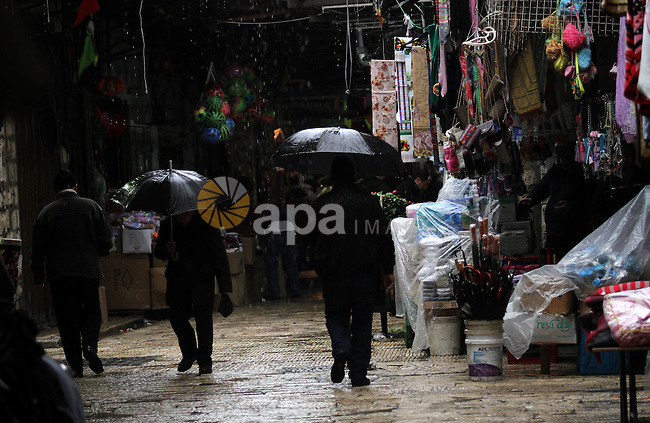 Palestinians walk with their umbrella under the rain, during a winter storm, in the West Bank city of Nablus, on December 18, 2016. Photo by Nedal Eshtayah