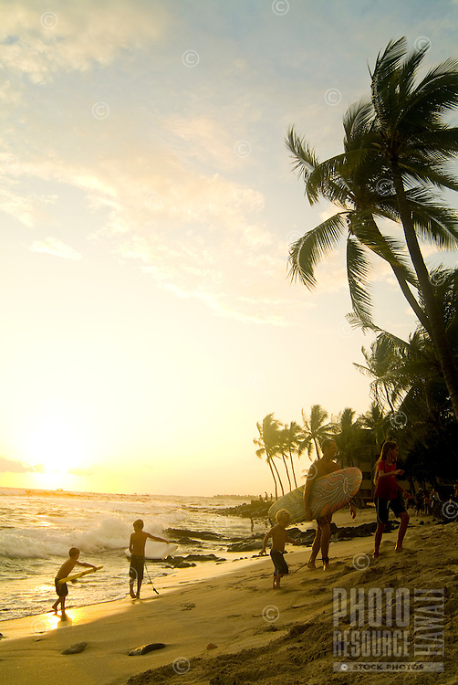 Children holding body boards look for a last wave at sunset while their dad walks from the shore holding a surfboard at Hano beach in Kona on the Big Island of Hawaii.
