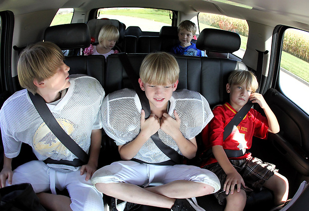 Counterclockwise from bottom left, Brayden, Justin, Keenan, Ethan and Ella Jacobs ride together on their way to a night of football practice and other activites.  Several times a week, their mother, Heather, loads up the family SUV for busy evenings of activities.  Heather lost her husband, Eric, in a plane crash in 2006 when she was eight months pregnant with their youngest, Ella, and has since been raising her five young children on her own.