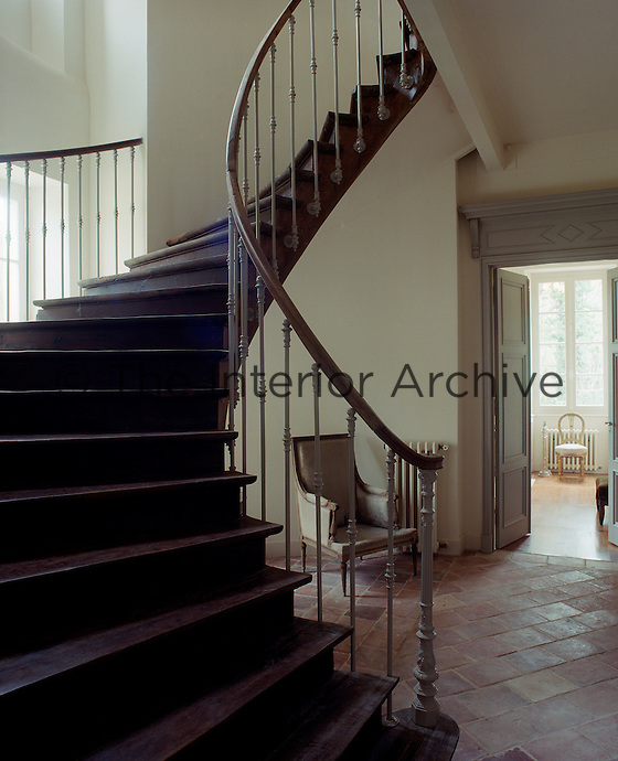 A graceful curved staircase spirals up from the faded terracotta tiles of the entrance hall