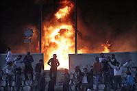 """GAN20- PORT SAID (EGIPTO), 1/02/2012.- Jóvenes egipcios se alejan de un fuego provocado en el estadio Cairo hoy, miércoles 1 de febrero de 2012 después de la cancelación del juego de fútbol entre los equipos Zamalek y Ismaily, en Port Said, Egipto. """"Los ultras del Al Masry saltaron al campo a linchar a los jugadores del Al Ahly"""", relató el joven Hosam Mohamed Mustafa, testigo de los graves disturbios que causaron la muerte de al menos 73 personas en Port Said (noreste de Egipto), tras el final del partido que enfrentaba a esos equipos. EFE/AHMED KHALED..."""