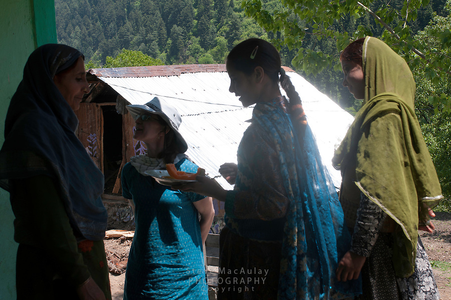 Traveler visiting with mother and young girls from a nomadic Bakarwal tribal family, Kashmir, India