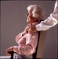 Seated older woman toching hand of younger woman<br />