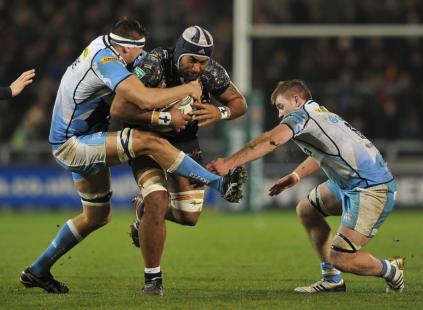 Montpellier's Aliki Fakate  is tackled by Sale Sharks' Tom Holmes  and James Doyle ..Rugby Union - Heineken Cup Pool 6 - Sale Sharks v Montpellier Herault - Friday 11th January 2013 - Salford City Stadium - Salford....