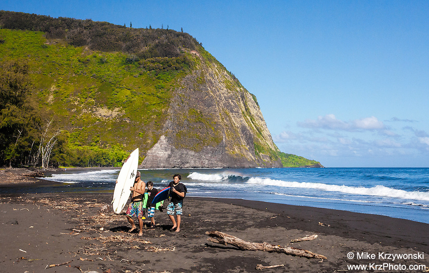 Kids w/ surfboards walking on beach in Waipio Valley, Big Island, Hawaii
