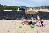 Andrew Crete (top), 6, James Crete, Charlotte Crete, 9, Olivia Crete, 3, and Karine Labelle, (from left) sit near a recently-repaired section of the parking lot embankment at Herring Cove Beach in the Cape Cod National Seashore outside of Provincetown, Mass., USA, on Fri., July 1, 2016. Portions of the parking lot have been closed after land eroded during storms earlier this year. The family is visiting Cape Cod from Saint-Sauveur, Quebec, Canada.