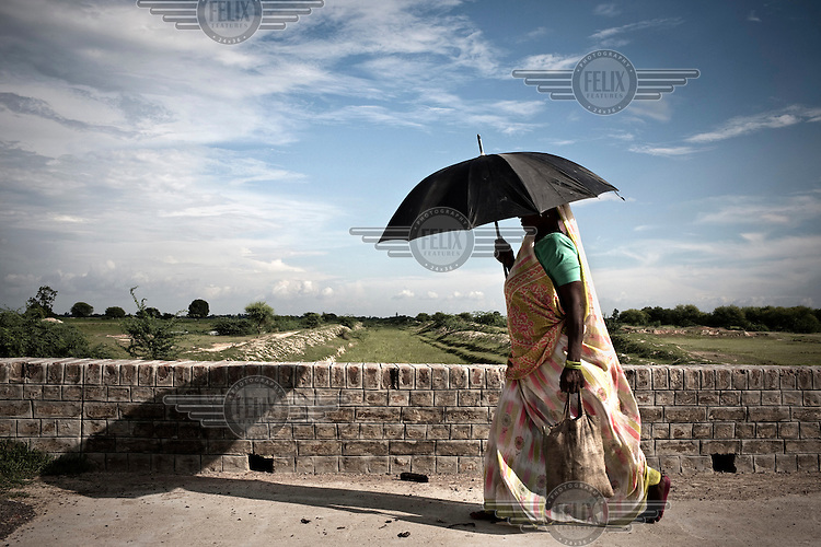 A woman, sheltering from the sun beneath an umbrella, walks past the dried up Mourawa Rajwaha Canal in Unnao.