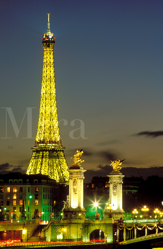 France, Paris, The Eiffel Tower illuminated at night and Pont Alexandre III