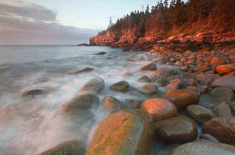 Waves splash against granite boulders at Boulder Beach and the Otter Cliffs, Acadia National Park, Maine, USA