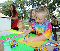 STAFF PHOTO ANDY SHUPE - Zippy Starr, 8, of Fayetteville colors a poster alongside friends during the All Children's Fair: Welcoming Feet in Motion Sunday, Sept. 21, 2014, at Walker Park in Fayetteville. The event was organized by the Coalition to Stand With All the Children as a way to raise money for and awareness of refugee children at the U.S. boarder with Mexico.