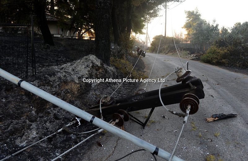Pictured: Damaged electricity pylons in the area.<br />Re: A forest fire has been raging in the area of Kalamos, 20 miles north-east of Athens in Greece. There have been power cuts, country houses burned and children camps evacuated from the area.