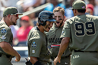 Vanderbilt Commodores third baseman Austin Martin (16) is greeted by his teammates on the bench after his second home run of the game against the Louisville Cardinals in the NCAA College World Series on June 16, 2019 at TD Ameritrade Park in Omaha, Nebraska. Vanderbilt defeated Louisville 3-1. (Andrew Woolley/Four Seam Images)