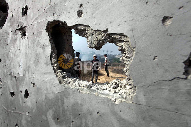 Palestinians inspect the place that was under an Israeli air strike in Dir al-Balah in the central Gaza Strip June 19, 2012. An Israeli army statement said the Israeli air force targeted Palestinian militants in the central Gaza Strip on Tuesday, who were responsible for firing rockets into Israel earlier today. Photo by Ashraf Amra