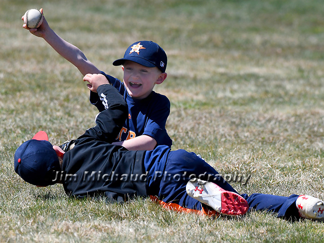 Mixing baseball with football, Chase Lingenfelter, 8, holds the ball he got to first after Wesley Fleury, both 8 and from Suffield, tackled him on a ball they both attempted to catch,  Saturday, April 21, 2018, during the opening day of Suffield little league. (Jim Michaud / Journal Inquirer)